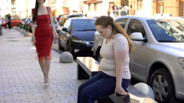 obese female looking enviously at slim beautiful lady passing by on street, diet - sovrappeso video stock e b–roll