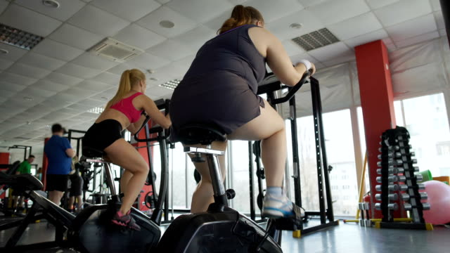 Obese female working on healthy body in gym, plump woman riding an exercise bike video
