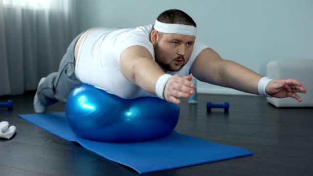 vidéos et rushes de homme de travailleur obèses pratique exercice statique, programme de formation de force - lutte