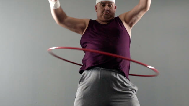 vídeos de stock, filmes e b-roll de homem obeso tentando torcer bambolê, sonhos de corpo saudável e em forma, emagrecimento - medicina esportiva