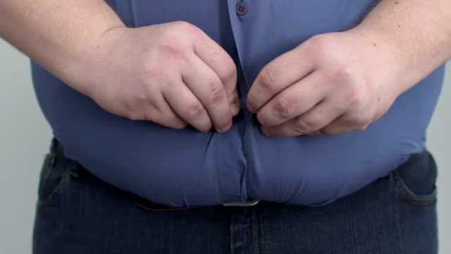 obese man buttoning shirt on enormous tummy, fight with insecurities, obesity - sovrappeso video stock e b–roll