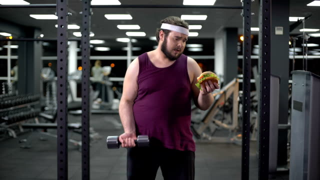 Obese man lifting dumbbell and holding burger in hand, life decision, motivation Obese man lifting dumbbell and holding burger in hand, life decision, motivation fat nutrient stock videos & royalty-free footage