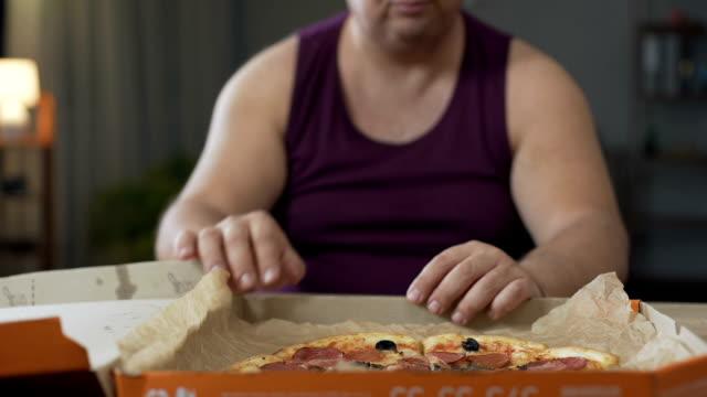 stockvideo's en b-roll-footage met zwaarlijvige man rondkijken en verslinden vette pizza's nachts, junkfood verslaving - dikke pizza close up