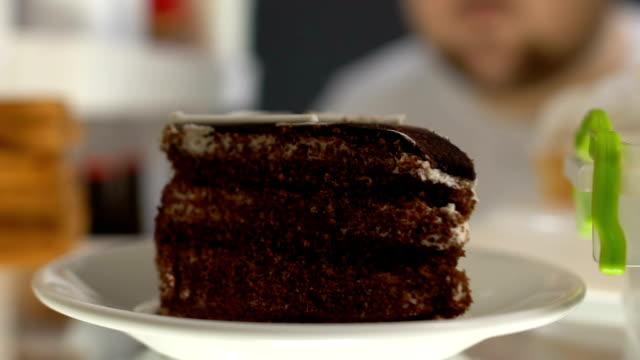 vídeos y material grabado en eventos de stock de hombre obeso tomando el plato de pastel de chocolate de nevera, diabetes de postre de azúcar - afección médica