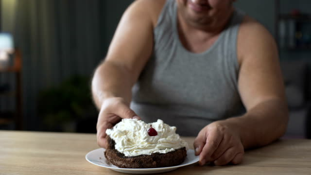 Obese person eating cake with whipped cream greedily and quickly, addiction video