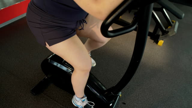 Obese woman pedaling on stationary bike in the sports club, weight loss workout video