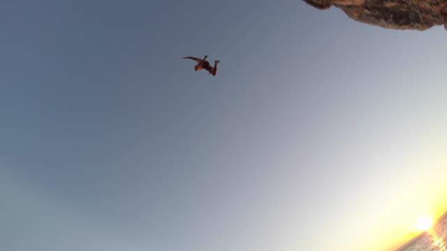 pov observing a water cliff jumper at sunset - утёс стоковые видео и кадры b-roll