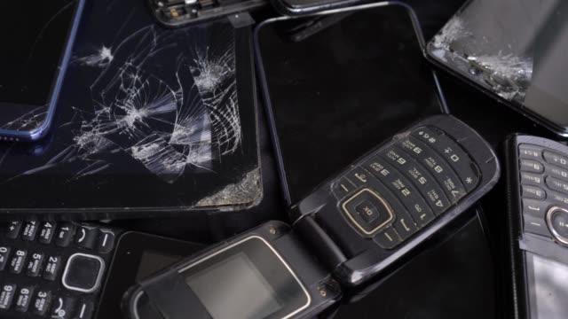 過時的舊手機和破碎的智慧手機與破裂的螢幕 - 電子工業 個影片檔及 b 捲影像