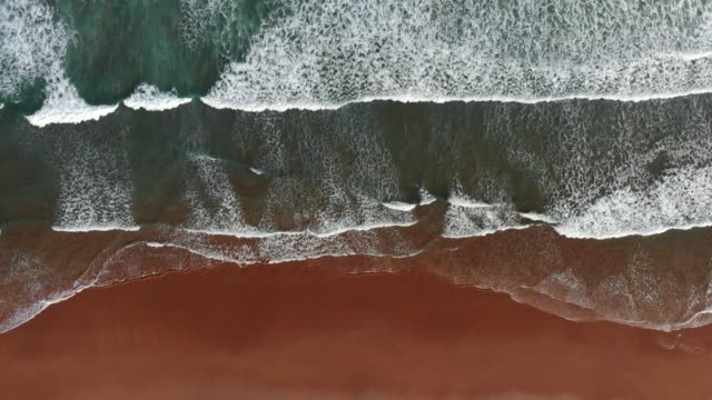 Ocean coast background. Foamy waves of turquoise ocean coming to a brown sand beach. Top down shot, UHD video