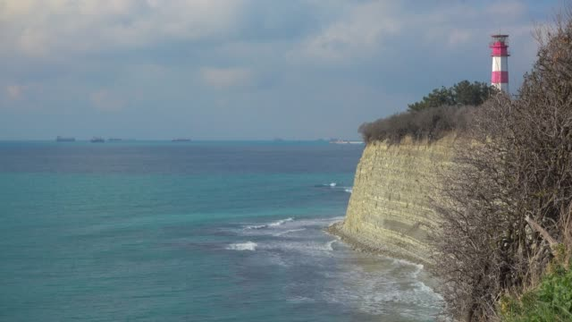 Ocean coast with lighthouse at beautiful day, ships in the distance. video