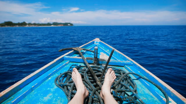 Ocean island of Bali. Boat tour. Young man in a boat on the ocean excursions. Stunningly clear ocean, year-round sunshine, paradise island - idyllic picture video