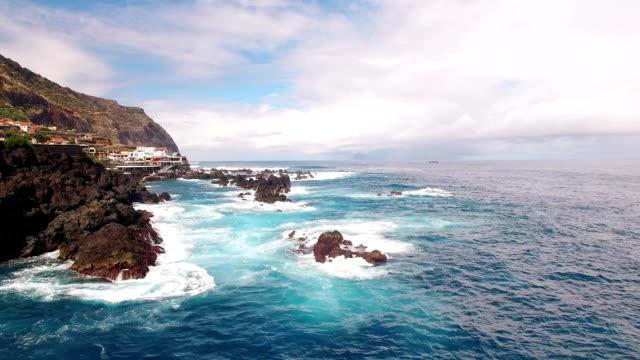 vídeos de stock e filmes b-roll de ocean near clifs of porto moniz madeira aerial view - ilha da madeira