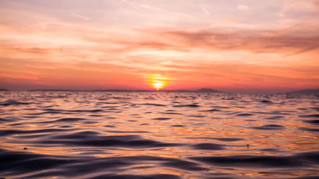 vídeos de stock e filmes b-roll de ocean slowly waving at sunset - linha do horizonte sobre água