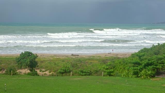 4k, ocean wave rolling towards sandy beach with green trees of taiwan island - юго восток стоковые видео и кадры b-roll