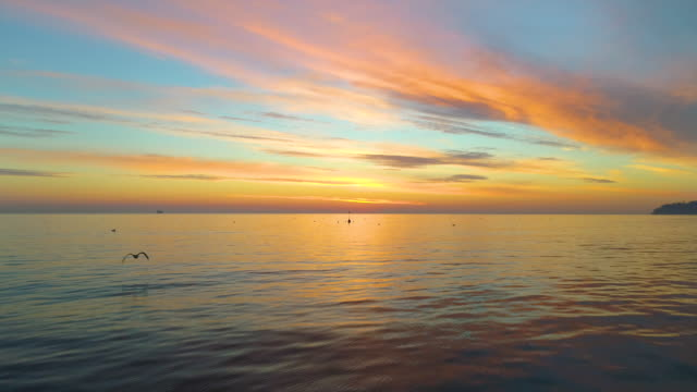Ocean waves and beautiful sunrise over the ripple water