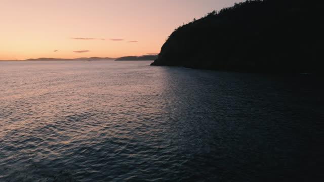 シーニックアイランドサンセットビューに飛ぶドローンでロッキーショアで壊れる海の波 ビデオ