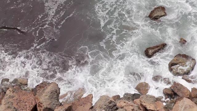 ocean waves crashing on the rocks,  aerial image of the waves crashing on the rocks in ibiza beach - formaggio comté video stock e b–roll