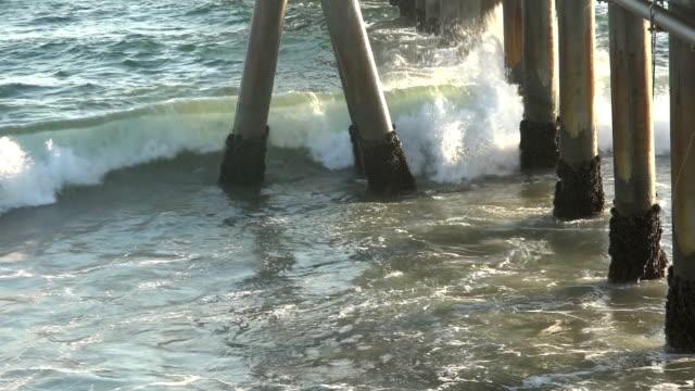 Ocean waves spray against a pier, slow motion