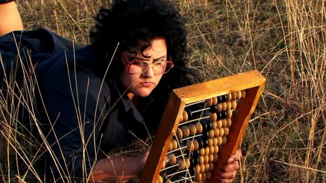 odd plus-sized woman in black playing with abacus at nature - abakus bildbanksvideor och videomaterial från bakom kulisserna