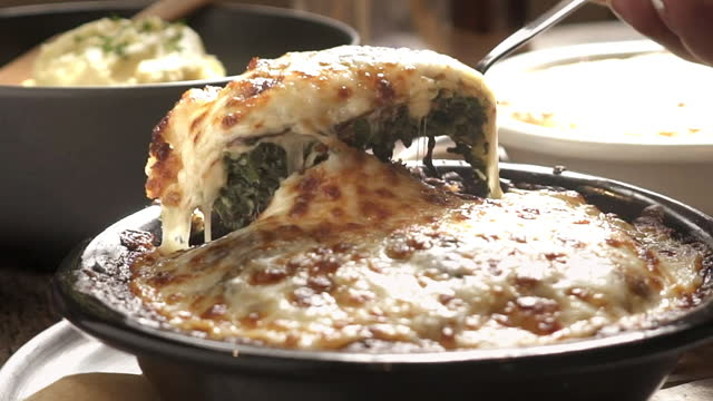 vídeos de stock e filmes b-roll de slow motion of baked spinach with cheese with stretching cheese with fork - assado no forno