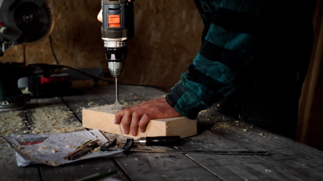 of carpenter's hands using drill on wooden plank of carpenter's hands using drill on wooden plank. FullHD shot cordless phone stock videos & royalty-free footage