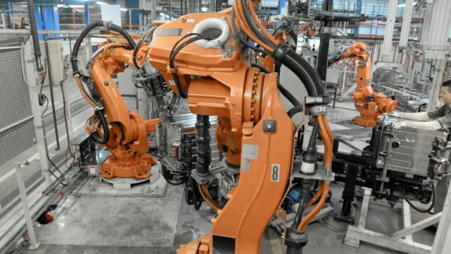 TIME-LAPSE of industrial robot operating in a factory Wide locked down time lapse shot of orange colored industrial robots performing their operations in a factory. Shot in Slovenia. robot stock videos & royalty-free footage