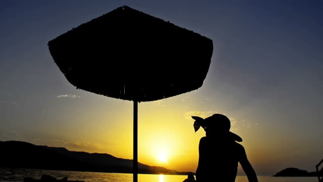 TRAVEL CONCEPT of Summer beach sunset with hat girl and straw umbrella silhouette video