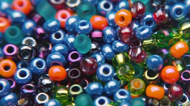 vidéos et rushes de du mouvement des perles colorées de bijoux - artisanat