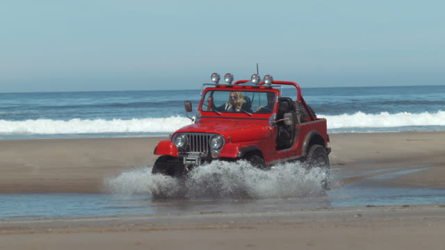 Off road vehicle driving through water in slow motion video