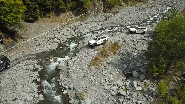 Off Road vehicles crossing wild mountain river. Aerial view of suv cars