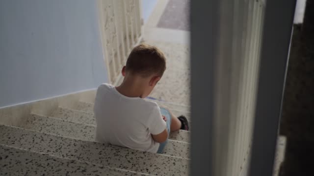 Offended child sitting on the stairs Boy sitting on the stairs at the entrance hall. Being offended he wants to sit alone boys stock videos & royalty-free footage
