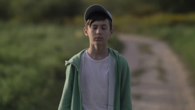 förolämpad fundersam pojke i en mössa går längs en länsväg vid solnedgången, närbild - walking home sunset street bildbanksvideor och videomaterial från bakom kulisserna