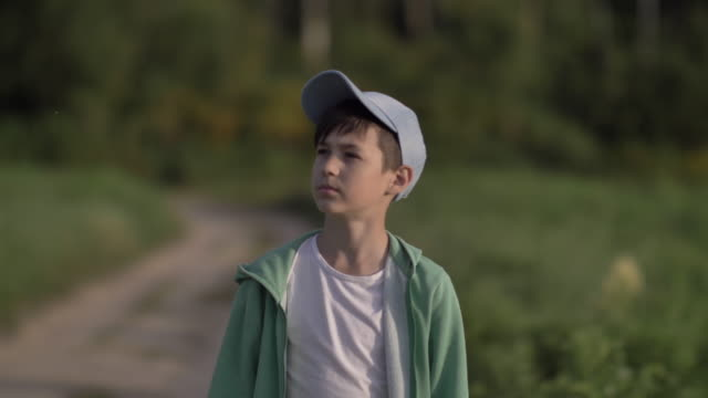 offended pensive boy in a cap is walking along a county road at sunset, close-up video