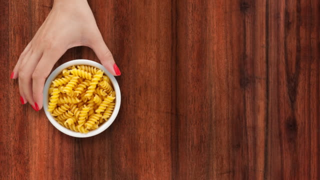 Offering fusilli Top view of woman hand sliding white bowl full of fusilli pasta over wooden background. Three options available for positioning the bowl: left, middle and right uncooked pasta stock videos & royalty-free footage
