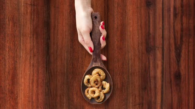 Offering homemade onion rings Top view of woman hand sliding wooden spoon full of homemade onion rings over wooden background. Three options available for positioning the spoon: left, middle and right onion ring stock videos & royalty-free footage