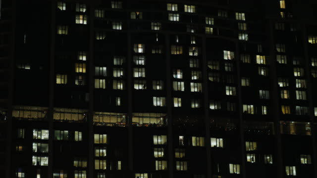 Office building in the dark. The windows are lit, people silhouettes are visible. Tilt shot video