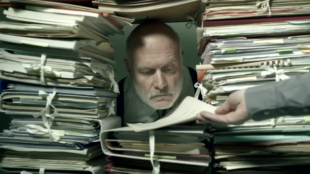 Office clerk working behind a wall of paperwork Office clerk working behind a wall of paperwork: he is peeking from a hole and stamping a document, bureaucracy concept overworked stock videos & royalty-free footage