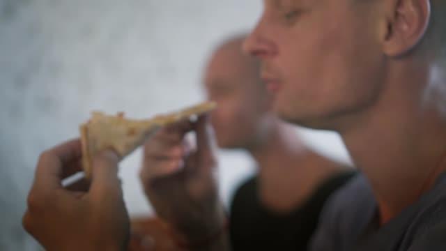 bürokollegen haben eine pizza, die ansicht zu schließen. freundliche mitarbeiter am tisch im büro, entspannende bestellt pizza und lebhaften gespräch während des essens - weißrussland stock-videos und b-roll-filmmaterial