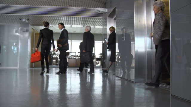 HD DOLLY: Office Corridor During Morning Rush Hour HD1080p: DOLLY shot of business people exiting an elevator and walking in all directions during morning rush hour. lobby stock videos & royalty-free footage