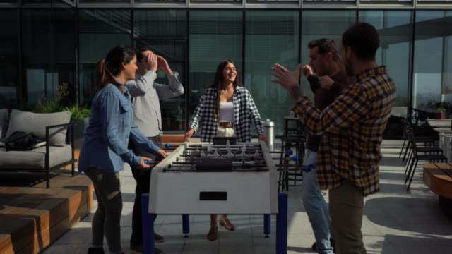 Office friends playing foosball at the terrace celebrating a score while other look disappointed - Lifestyles Office friends playing foosball at the terrace celebrating a score while other look disappointed coworking stock videos & royalty-free footage