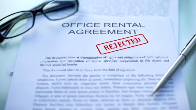 vidéos et rushes de contrat de location de bureau a rejeté, les main piétinement sceau sur le document d'entreprise, fermer - notaire