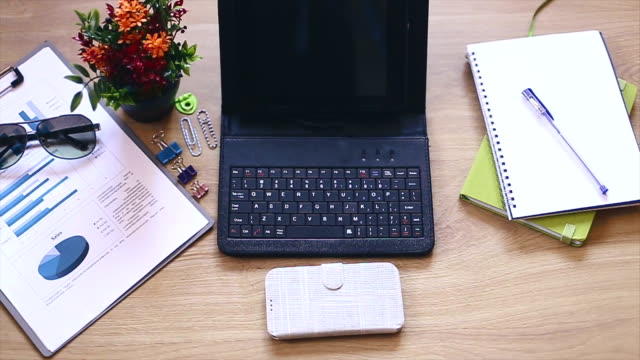 Office supplies and gadgets on wooden table video