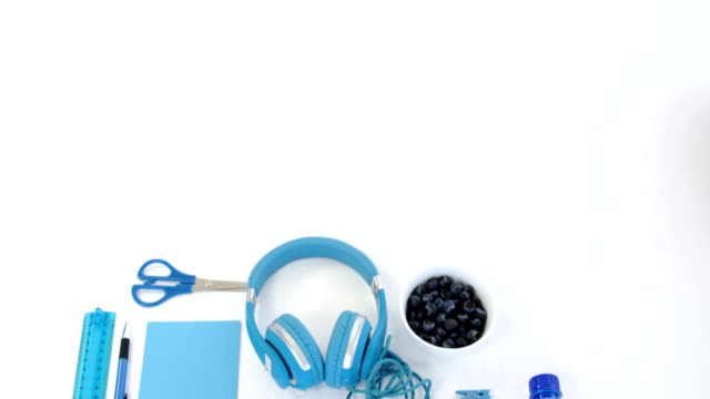 Office supplies, water bottle and blue berries on white background 4k video