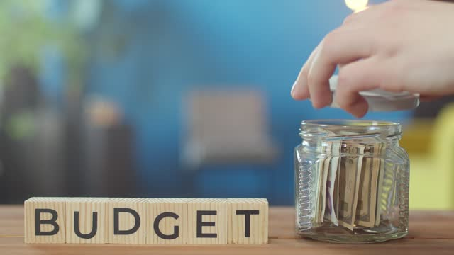 Office table are wooden cubes with the inscription budget, next to it is a glass jar that opens the hand and puts a wad of cash in it. Savings concept