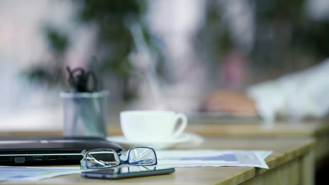 office work, laptop, smartphone and eyeglasses lying on table. workplace - scrivania video stock e b–roll