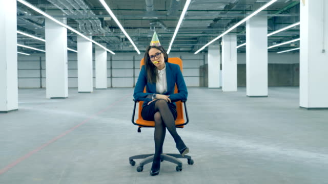 Office worker blows a penny whistle, wearing a birthday cap. Boring birthday concept.