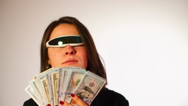 Office worker holds a pack of US dollars in his hands and shows them to camera. An office worker holds a pack of US dollars in his hands and shows them to the camera. Concept of financial dominance of a woman. domination stock videos & royalty-free footage