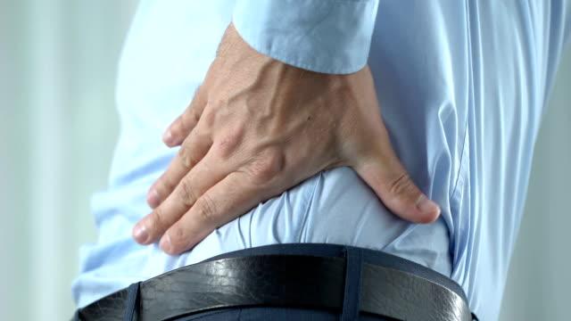 Employé de bureau dans 40 ans sensation forte douleurs dorsales, debout, le mode de vie sédentaire - Vidéo
