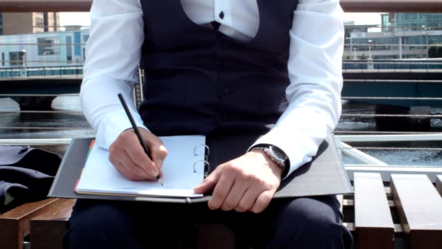 Office Worker Sitting On A Bench Writing Notes. video