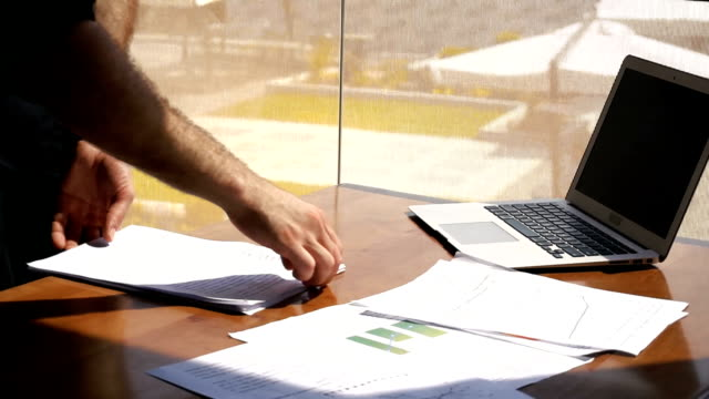 Office worker sorting papers on table near laptop video